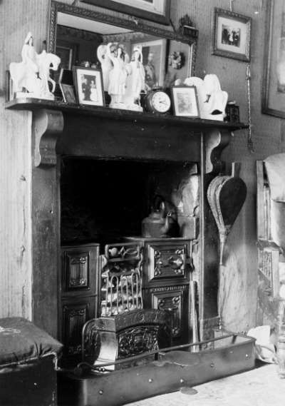 Fire range with a kettle, bellows hanging by the side and frames, a clock and  ornaments on the mantle piece above