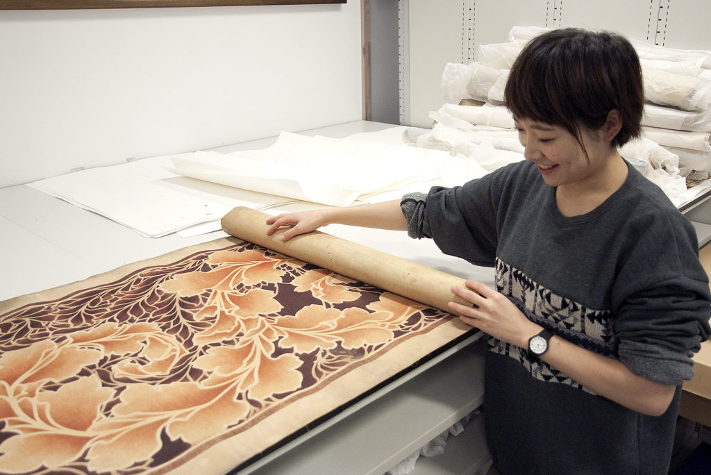 student Naoko Nomoto unrolling grasspaper