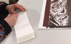 drawing in a notebook looking at a katagami stencil
