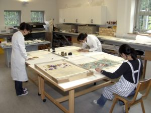 Image of 3 museum volunteers in white coats undertaking conservation of inter-war Silver Studio designs on paper